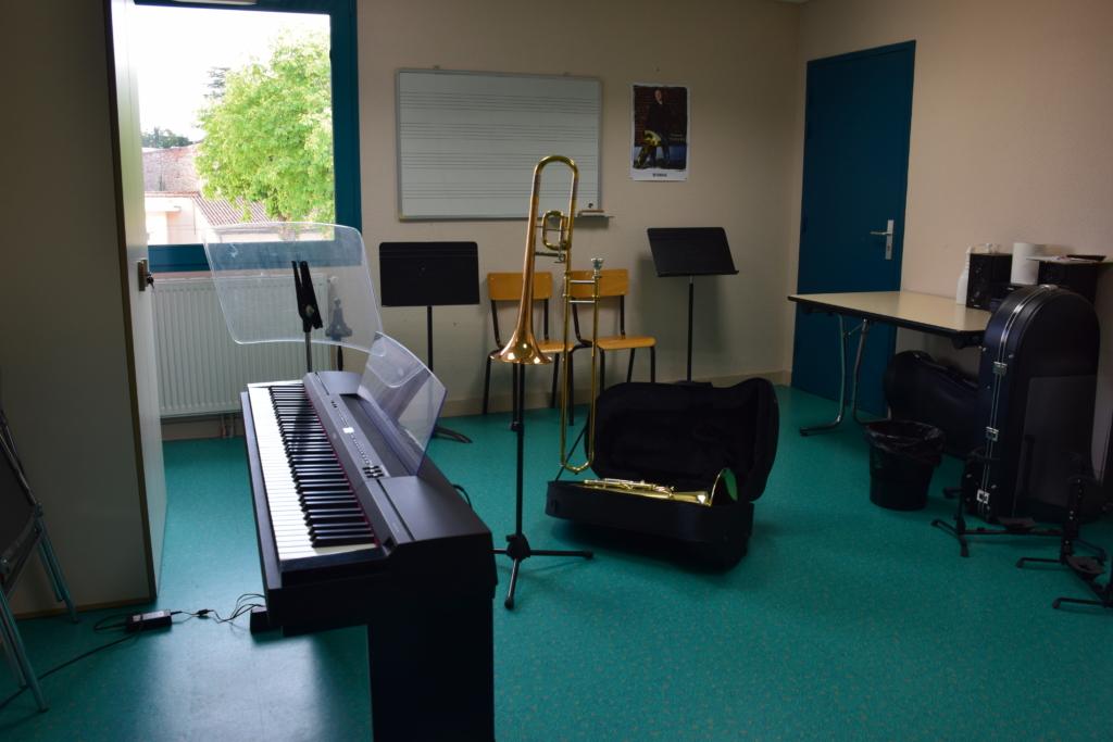 Salle de musique avec un piano, un saxophone et un trombone rangé dans sa malette