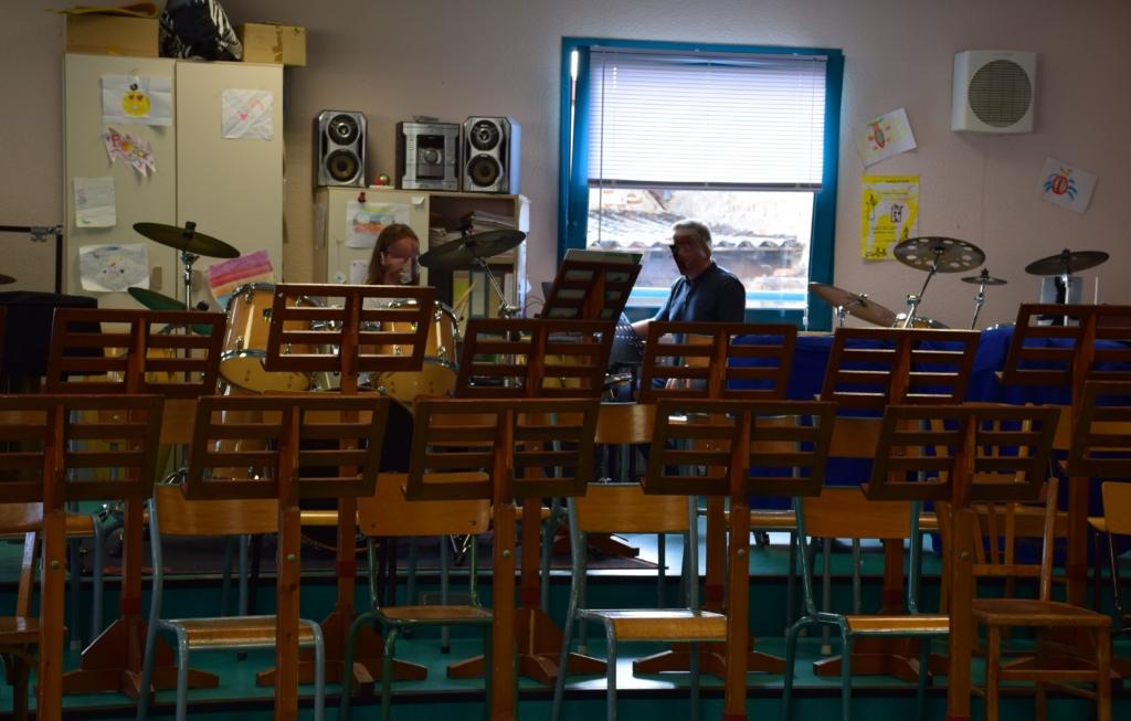 Cours de percussion donné par un professeur au second plan à son élève, une jeune fille au premier plan
