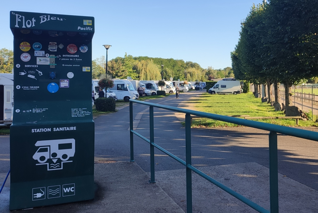 Vue de l'aire de camping car avec la borne de recharge au 1er plan et les véhicules au second garés