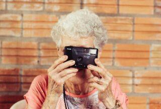 Une grand-mère prend une photo avec un appareil photo avec un mur en brique en fond